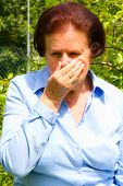 stock photo of hay fever  - Portrait of senior woman sneezing with hay fever in her garden - JPG