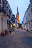 MAASTRICHT, NETHERLANDS - SEPTEMBER 7, 2013: Rechtstraat and the spire of St. Maartenskerk church. B