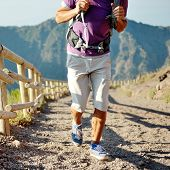 Hiker With Backpack Running On A Path Of Mountain