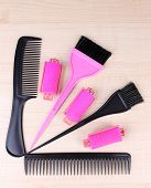 Professional hairdresser tools - comb, scissors and curlers on light wooden background