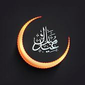Golden crescent moon with arabic islamic calligraphy of text Eid Mubarak on black background.