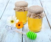 Jar full of delicious fresh honey and wild flowers on wooden table