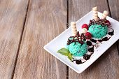 Tasty ice cream with chocolate decorations and sauce plate, on color wooden  background