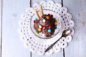 Chocolate ice cream with multicolor candies and wafer rolls in glass bowl, on color wooden backgroun