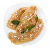 Sweetened fried banana on plate, isolated on white