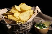 Tasty potato chips in metal basket  on wooden table with dark light