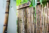 Tropical outdoor shower surrounded with bamboo walls