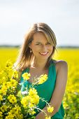stock photo of rape  - blond woman in a rape field - JPG