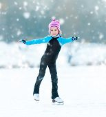cute  cheerful little girl in thermal suits skating  outdoors