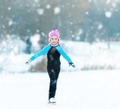 happy cheerful little girl in thermal suits skating  outdoors