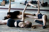 stock photo of  dancer  - Three young ballet dancers on the floor rehearsing position in the ballet