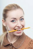 Excited attractive woman biting pencil