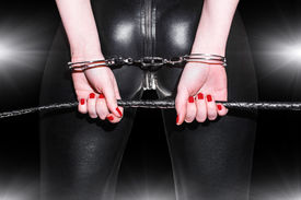 stock photo of sado-masochism  - Woman ass closeup in latex catsuit whip and handcuffs bdsm - JPG
