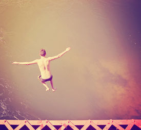 picture of trestle bridge  - a boy jumping of an old train trestle bridge into a river done with a retro vintage instagram filter - JPG