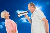 Man shouting at his partner through megaphone against bright blue sky with clouds