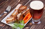 Grilled pork ribs, glass of beer and fresh carrot on wooden background