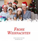 Extended family in Christmas hats with gift boxes in living room against christmas greeting in german