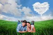 Young couple lying on floor smiling against cloud heart