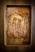 picture of bacon strips  - Strips of cooked bacon lined up on an old baking sheet - JPG