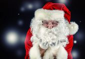 Close-up portrait of Santa Claus blowing on snowflakes. Christmas time. Black background.