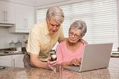 Senior couple looking up medication online at home in the kitchen