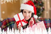 Smiling brunette holding gift and shopping bag at christmas against fir tree forest and snowflakes