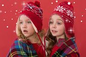 Festive little girls under a blanket against snow