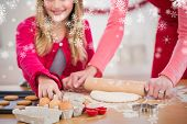 Festive mother and daughter making christmas cookies against snowflakes