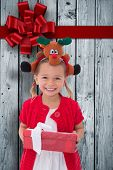 image of rudolph  - Cute little girl wearing rudolph headband against wood with festive bow - JPG