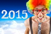 Geeky hipster in afro rainbow wig against blue sky over clouds