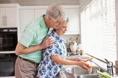 Senior couple washing vegetables at sink at home in the kitchen