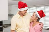 Senior couple wearing santa hats at home in the kitchen