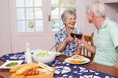 Senior couple having lunch together at home in the kitchen