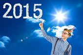 Geeky hipster wearing party hat pointing against bright blue sky with clouds
