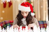 Brunette looking in gift bag at christmas against fir tree forest and snowflakes