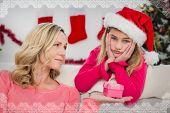 Festive mother and daughter with gift against snowflake frame