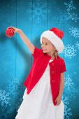 Cute little girl wearing santa hat holding bauble against snowflake pattern on blue planks