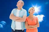 Thinking older couple with arms crossed against bright blue sky with clouds