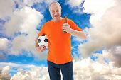 Mature man in orange tshirt holding football and beer against blue sky with white clouds