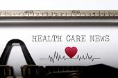stock photo of beating-heart  - Health care news printed on an old typewriter with heart beat pulse sketch - JPG