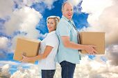 Happy older couple holding moving boxes against blue sky with white clouds