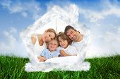 Happy family reading a book on bed against field of grass under blue sky