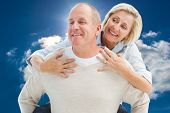 Happy mature man giving piggy back to partner against blue sky with clouds and sun