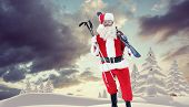 Santa claus holding ski and ski poles against snowy landscape with fir trees