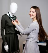 pic of dress mannequin  - Young woman looking at necklace on mannequin in showroom - JPG