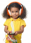 Cute african american small girl listening to music on a cellphone using big orange headphones isolated on white
