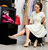 Young woman choosing shoes in a showroom