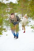 Young guy running from his girlfriend throwing snowball at him