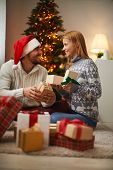 Cheerful couple opening packages with presents on Christmas night
