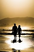 A couple walking at the beach of Byron Bay, Australia at sunset